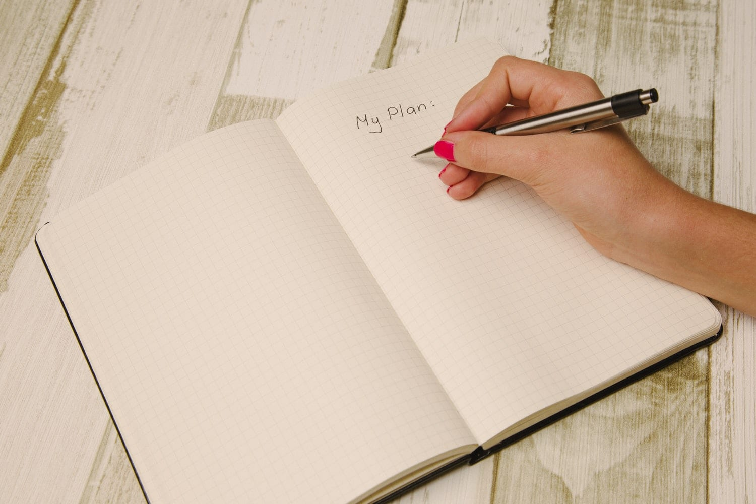 Writing domestic cleaning plan on notebook